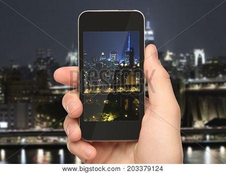 Hand holding smartphone on illuminated night city background. Urban concept