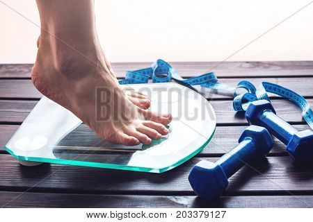 Female Feet Standing On Electronic Scales, Dumbbells And Measuring Tape. Concept Of Slimming And Wei