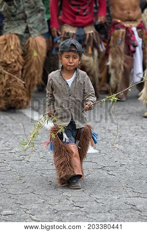 June 29 2017 Cotacachi Ecuador: kichwa indigenous child wearing chaps dancing on the street during Inti Raymi festival