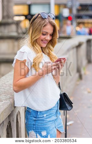Young Woman Stands With A Phone At A Bridge Railing