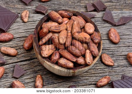 Cacao beans in a bowl with dark chocolate on wooden table