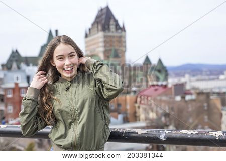 A Quebec City scape with Chateau Frontenac and young teen enjoying the view.