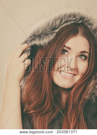 Happy woman wearing dark poncho coat with furry hood. Winter fashion trendy clothing outfits concept.