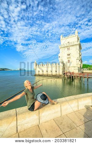 Happy woman with open arms at Belem Tower refleting. Torre de Belem is Unesco Heritage and symbol of Lisbon, in Belem District on Tagus River. Female tourist enjoys of most visited tourist attraction.