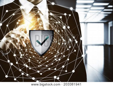 Businessman pointing at abstract glowing network with antivirus shield. Web crime concept