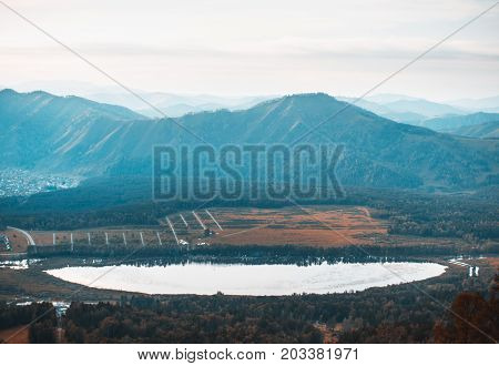 View from high above of Manzherok lake surrounded by Altai mountains and meadows with settlement on the right overcast autumn evening Russia