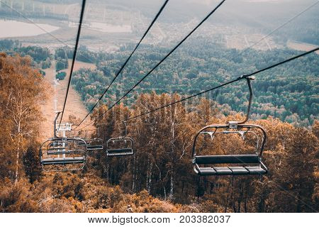 View from high point of empty ropeway stretching down among autumn trees and meadows with Manzherok lakeand settlement of the same name in distance on overcast day Altai mountains Russia