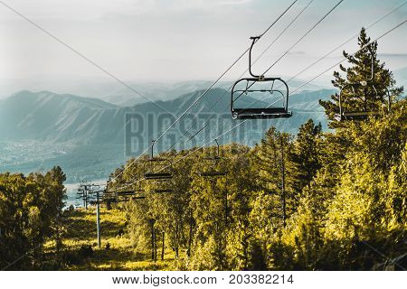 Landscape with cableway with empty seats stretching down over summer hills meadow and trees of Altai mountains in Manzherok district with mountain ridge in background Russia