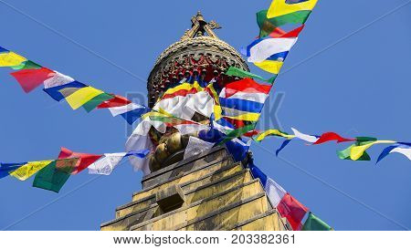 Prayer colorful flags flying from the Buddhist Stupa a place of holy worship. Buddhist Temple in the Kathmandu valley Nepal
