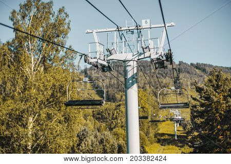 View of cableway stretching above hills: metal bearing support with wheels in foreground summer hills and meadows overgrown with greenery in background; Altai mountains Manzherok district Russia