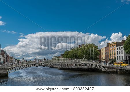 Dublin Ireland - August 7 2017: Historic metal Ha'penny pedestrian bridge over Liffey River under blue sky with giant white cloud. People walking. Facades along the river.
