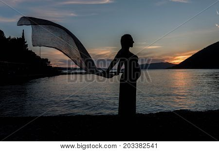 Silhouette of pregnant woman holding scurf in the sunset
