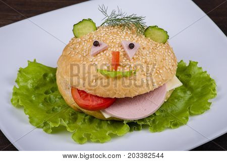 Fun food for kids - hamburger looks like a funny muzzle in white plate close up