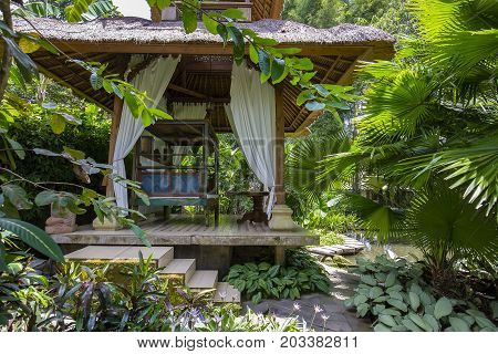 Wooden arbor for relaxing in the tropical garden. Island Bali Ubud Indonesia