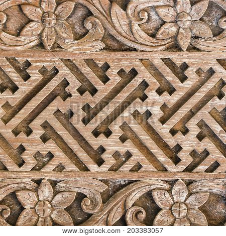 Detail of a beautiful carved wooden door of a temple in Ubud Bali Indonesia . Close up