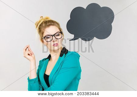 Business woman wearing blue jacket and eyeglasses intensive thinking finding great problem solution black thinking or speech bubble next to her.