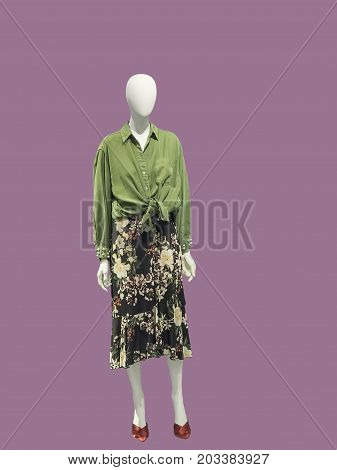 Full-length female mannequin dressed in green shirt and skirt isolated. No brand names or copyright objects.