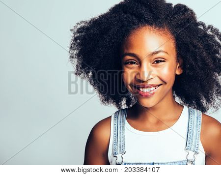 Smiling African Girl With Curly Hair Against A Gray Background