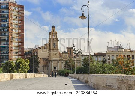 VALENCIA, SPAIN - MAY 18, 2017: It is a medieval Serranos bridge and the church of Salvador and Santa Monica.
