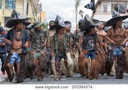 June 29 2017 Cotacachi Ecuador: kichwa indigenous people wearing chaps and large hats dancing on the street during Inti Raymi festival
