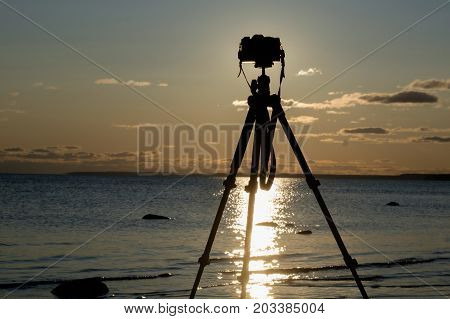 Silhouette camera with tripod over sunset near sea water.