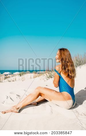Young woman in swimwear with sand on tropical beach. Summer woman body