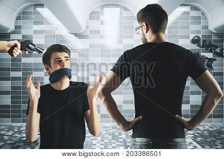 Young man with tied mouth threatened with gun in grungy underground interior. Crime concept