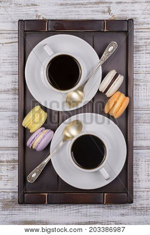 Two cups of coffee spoon and macaron cakes on tray on white wooden table. Lifestyle concept. Close up. Top view