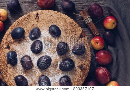 Pie with fresh fruits on a dark wooden table