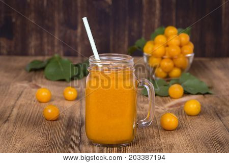 Healthy eating food dieting and vegetarian concept - glass of juice smoothie shake from yellow plum and ripe yellow plum on a vintage wooden table. Bio healthy food and drink. Organic diet.