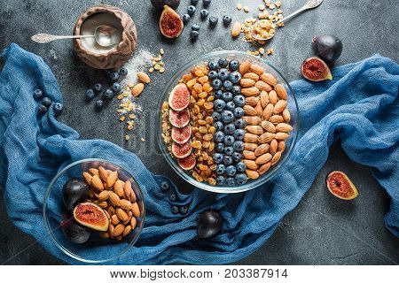 Breakfast with muesli, berries, figs and nuts on dark background. Flat lay, Top view