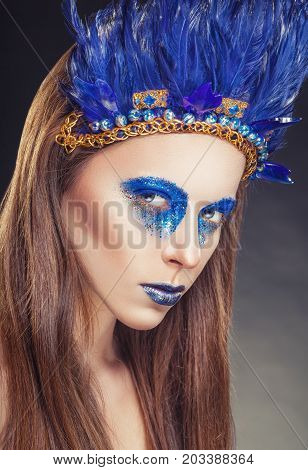 Fashion makeup in the American Indian style. Attractive woman with make-up with bright blue feathers