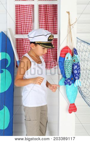 MOSCOW - OCT 04, 2016: Little admiral (with model release) in a white cap and t-shirt standing at the window near colored textile fish