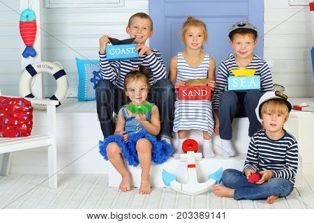 MOSCOW - OCT 04, 2016: Five happy children (with model release) with colored paper boats and bars with inscriptions coast, sand, sea sitting in the porch with lilac door