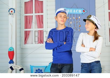 MOSCOW - OCT 04, 2016: Young cabin boy and girl (with model release) in cap with the inscription Admiral crossed their arms coquettishly looking at each other in front of white house with purple door