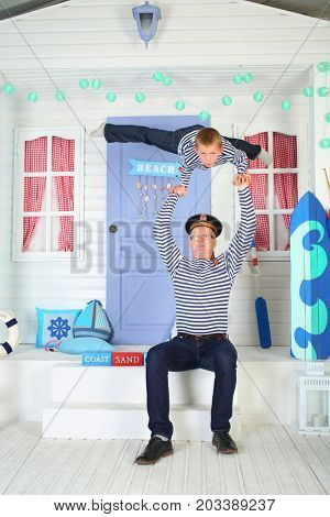 MOSCOW - OCT 04, 2016: Father (with model release) in cap with inscription Pacific Fleet with son (with model release) in vests perform acrobatic support at arms on porch of the white house with door