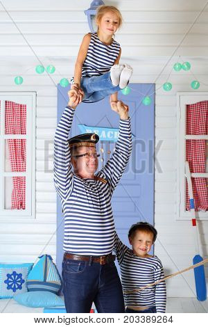 MOSCOW - OCT 04, 2016: Father (with model release) in cap with inscription with daughter (with model release) perform acrobatic support at arms near son (with model release) in front of the lilac door