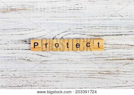 PROTECT word on block concept. PROTECT word made with wooden blocks on the table