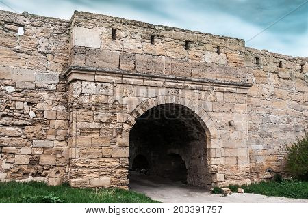 The medieval ruins of the fortress. The passage in the form of an arch made of stones.