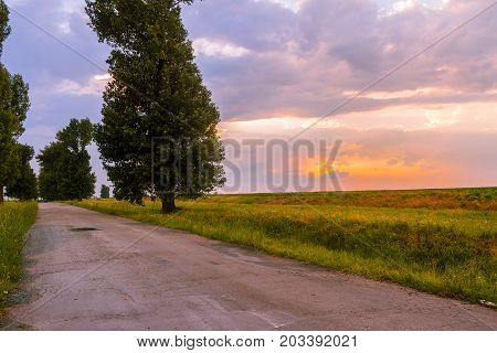 Rural road and sunset sky with clouds in countryside.