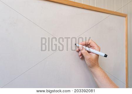 Female hand writing on whiteboard with felt tip pen