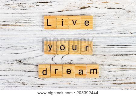 The words live your dream made of letters on wooden blocks.