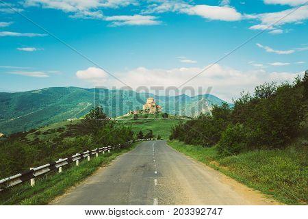 Mtskheta, Georgia. Open Road Going To Jvari, Georgian Orthodox Monastery, World Heritage By UNESCO. Beautiful Mountain Landscape And Blue Cloudy Sky Background.