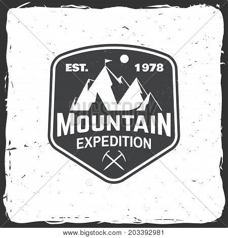 Mountain expedition badge. Vector illustration. Concept for shirt or logo, print, stamp or tee. Vintage typography design with ice axe and mountain silhouette.