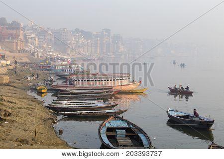 VARANASI INDIA - JANUARY 25 2017 : Morning view at holy ghats and wooden boats at the river ganges of Varanasi India