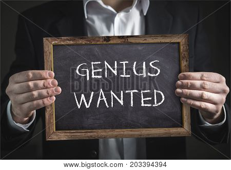 Businessman holding in hand an blackboard with writte genius wanted poster