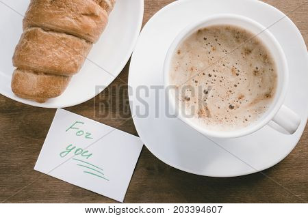 Cappuccino or coffee latte with foam in white cup and croissant on wooden table. Inscription For you.