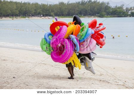 GRAND BAY MAURITIUS - MARCH 07 2017 : Unknown seller of inflatable toys and swimming laps goes along the beach in island Mauritius