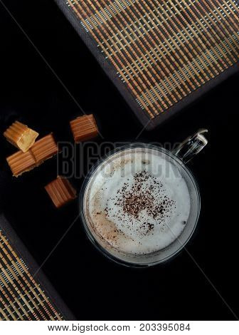 A cup of cappuccino , cappuccino with sweets, cappuccino with cinnamon on the top, delicious drinks