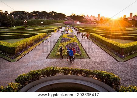 Curitiba, Brazil - July 21, 2017: People walk in the famous park of Botanical Garden during sunset. The garden was opened in 1991 and covers 240.000 m2 in area.